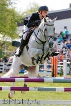 Reportage - Springreiterin und Pferd mitten im Sprung